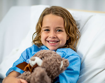 Child smiling holding a stuffed bear