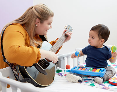 Cassi Crouse playing guitar for a child
