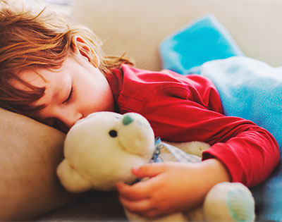 Child sleeps with teddy bear