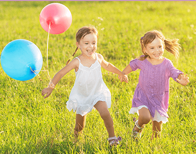 Two young girls with balloons for Stanford Children's Health Clubfoot program