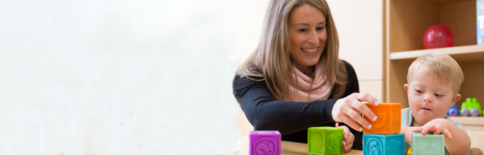 Stanford Children's Health Development Pediatrics therapist with young child playing with blocks