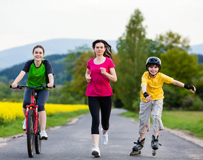 Family running and biking on road