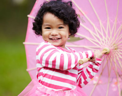 Young girl twirling a pink umbrella