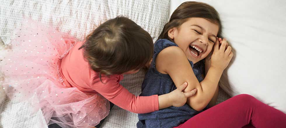 Two toddler kids playing together on a bed