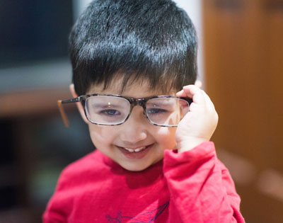 Young boy with glasses in a red shirt