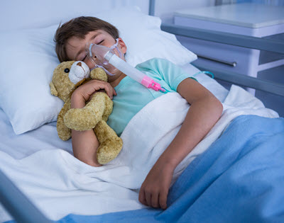 Child in hospital bed with teddy