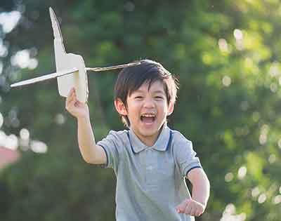 Boy running with toy plane