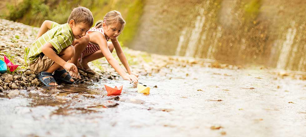 Boy and girl playing with paper boats in stream