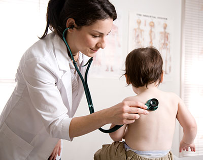 Pediatrician performing check up on child using stethoscope
