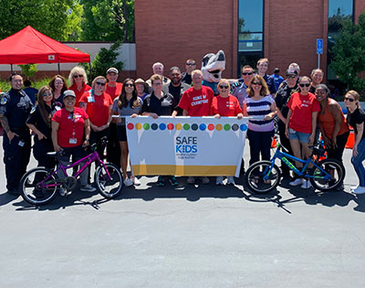 Safe Kids Coalition group photo with banner and bikes