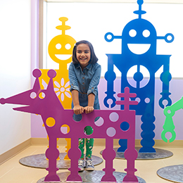 Young girl in front of robot art at Lucile Packard Children's Hospital Stanford