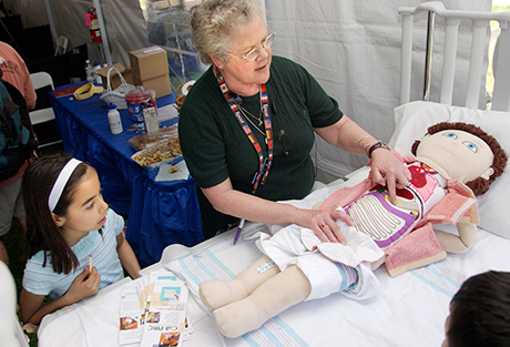 child with nurse examines doll on patient bed