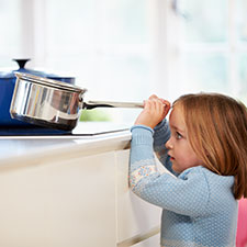 Child grabbing pan from stove