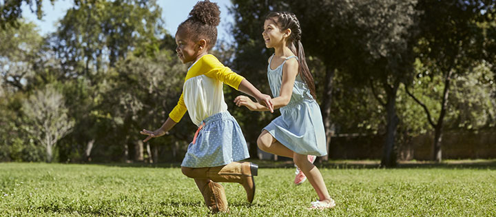 two girls skipping across the lawn