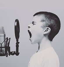Boy yelling into microphone