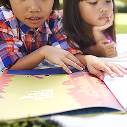 Two kids reading a book