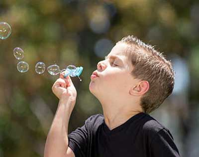 A young boy, from Stanford Children's Health Aerodigestive Program, blowing bubbles at Lucile Packard Children's Hospital Stanford