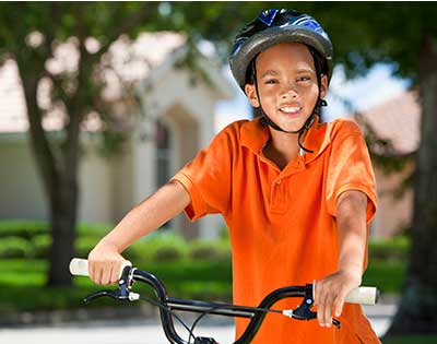 Boy on bike with helmet at Stanford Children's Health