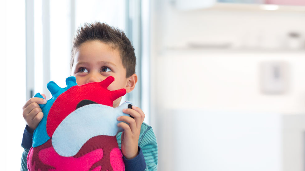 Young boy holding a toy close to his face