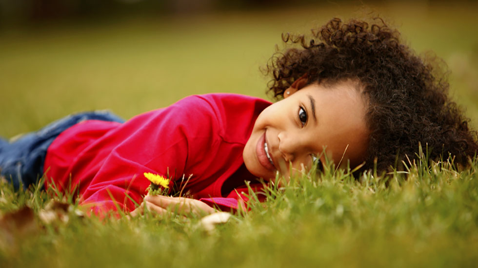 Young child laying on the green grass