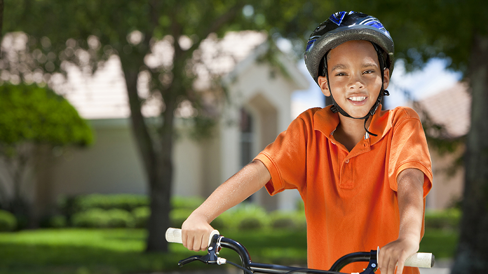 Boy on his bicycle, wearing his bicycle helmet