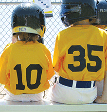 Children in baseball uniforms, sitting on a bench