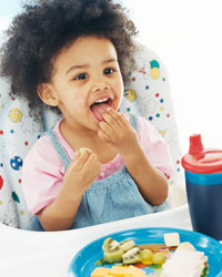 Picture of a young boy feeding himself from his highchair