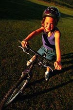 Picture of a young girl, wearing a helmet, riding a bicycle